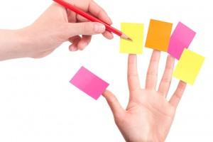 mano con lápiz anotando en otra mano que en cada dedo tienen una hoja pegada