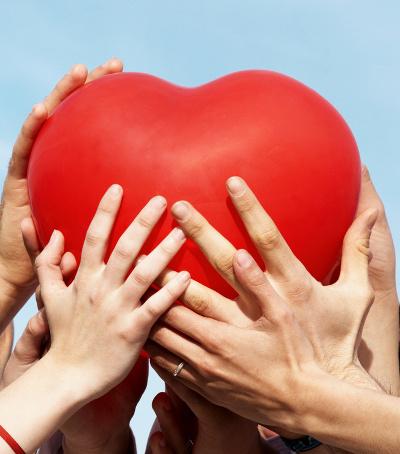 Manos sotienen un globo en forma de corazón