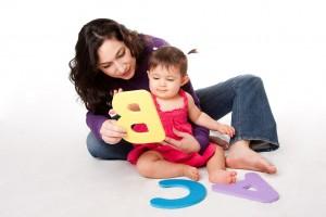 Niiño jugando con recortes con forma de letras en el fondo una mujer