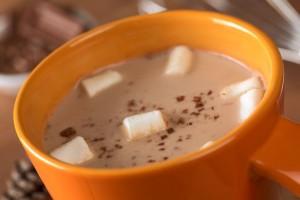 Chocolate caliente en taza naranja con malvaviscos