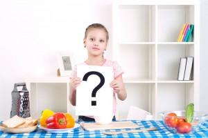 Niña en una cocina con un letrero de pregunta