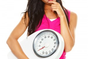 Mujer cargando una báscula para medir peso personal