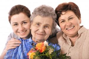 Bisabuela sonrioendo recibiendo flores de con bisnieta e hija