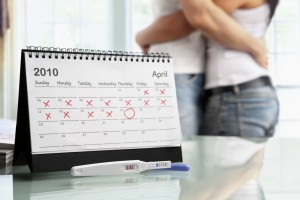 Calendario y prueba de embarazo con una pareja abrazandose en el fondo