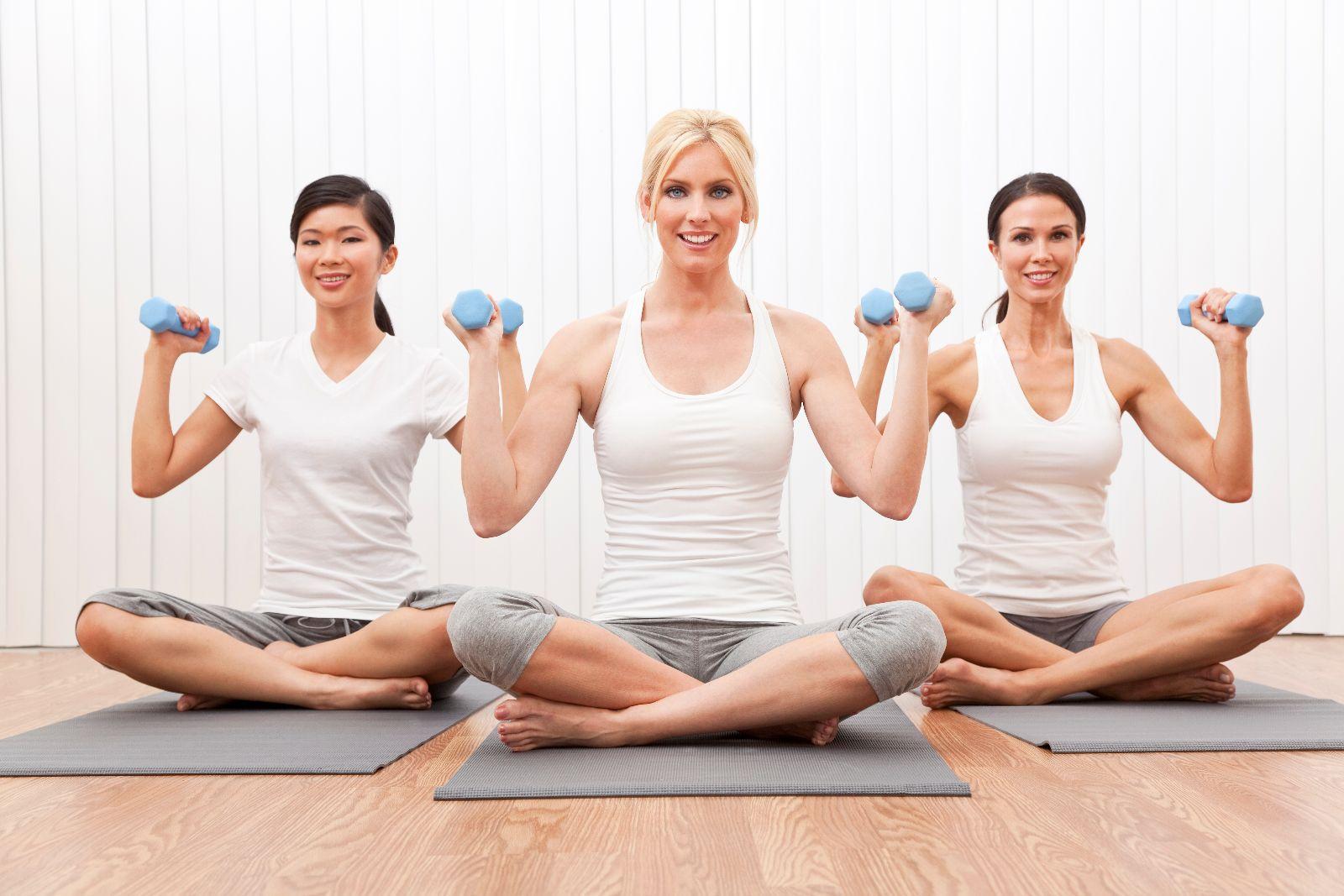 Mujeres con pesas en posición de loto