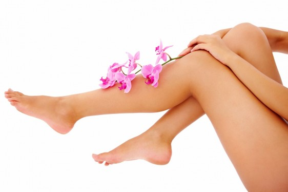 Woman holding orchid branch over her legs copyspace