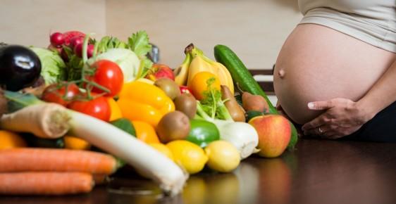 mujer embarazada con vegetales y frutas