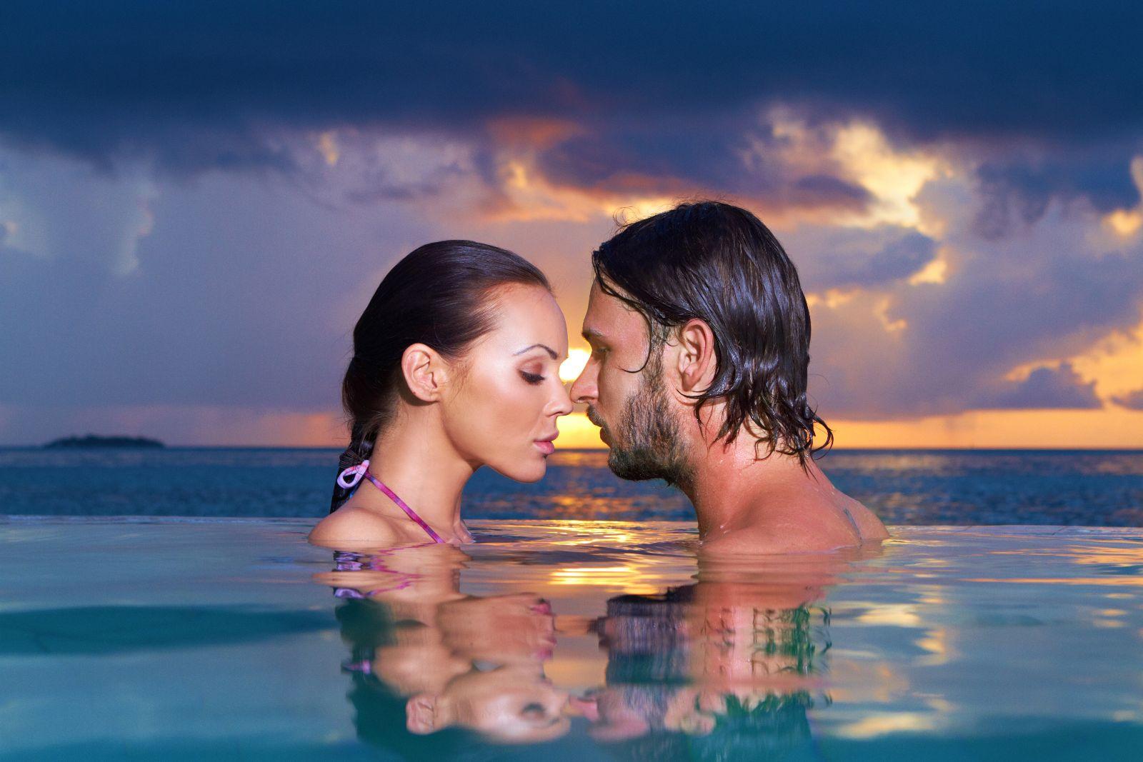 pareja abrazandose en el agua con una playa en el fondo