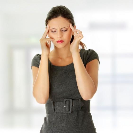 Mujer con vestido gris tocandose la cabeza como señal de dolor