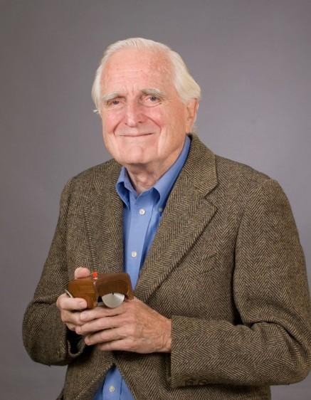 Douglas Engelbart con un prototipo del ratón de computadora en la mano.