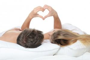 Pareja acostada en la cama con la manos haciendo unsimblo de corazón