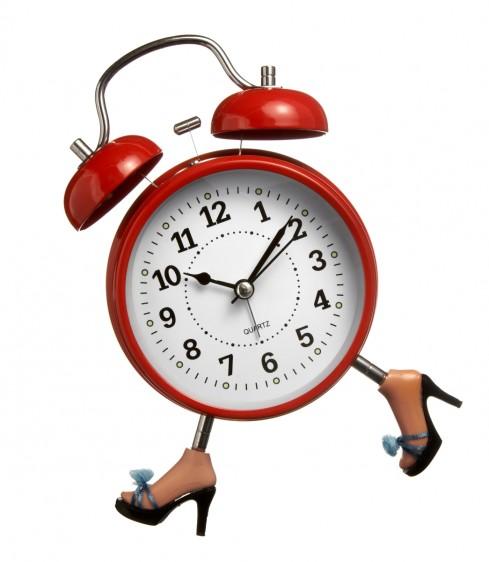 Reloj roko con piernas de mujer con tacones en fondo blanco