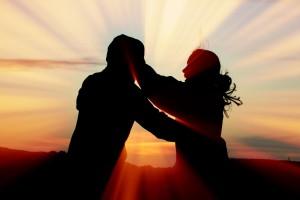 sombra de una pareja abarzandose con un fondo de amanecer