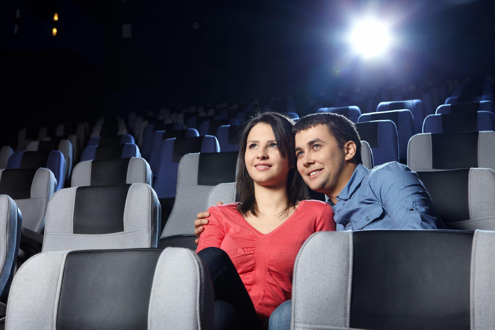 Pareja abrazandose sentados en asientos de cine