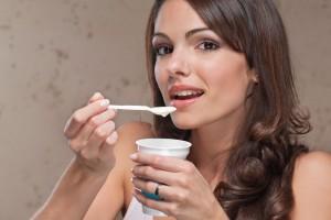 Mujer comiendo con una cuchara yogurt