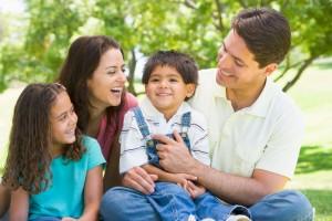 Familia sentada en un parque sonriendo