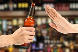 Dos manos una ofrciendo una botella oscura y otra en señal de rechazo