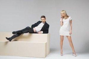 Mujer sensua de pie con hombre a su lado acostado