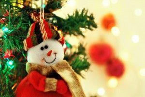 Muñeco de hombre de nieve sonriendo con árbol de navidad al fondo