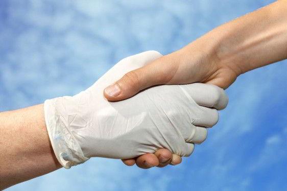 Mano con guante de latex dando un saludo a itra mano con el cielo azul de fondo