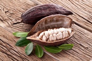 fruto de Cacao en una mesa sobre sus hojas abierto a la mitad mostrando las semillas