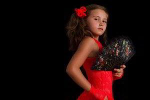 Niña con vestido rojo y abanico en postura de baile flamenco