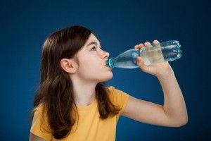 Niña con camisa amarilla tomando agua fondo azul