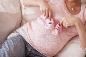 Acercamiento a mujer embarazada con blisa rosa y jeans sostiene unos zapatitos de bébe rosa