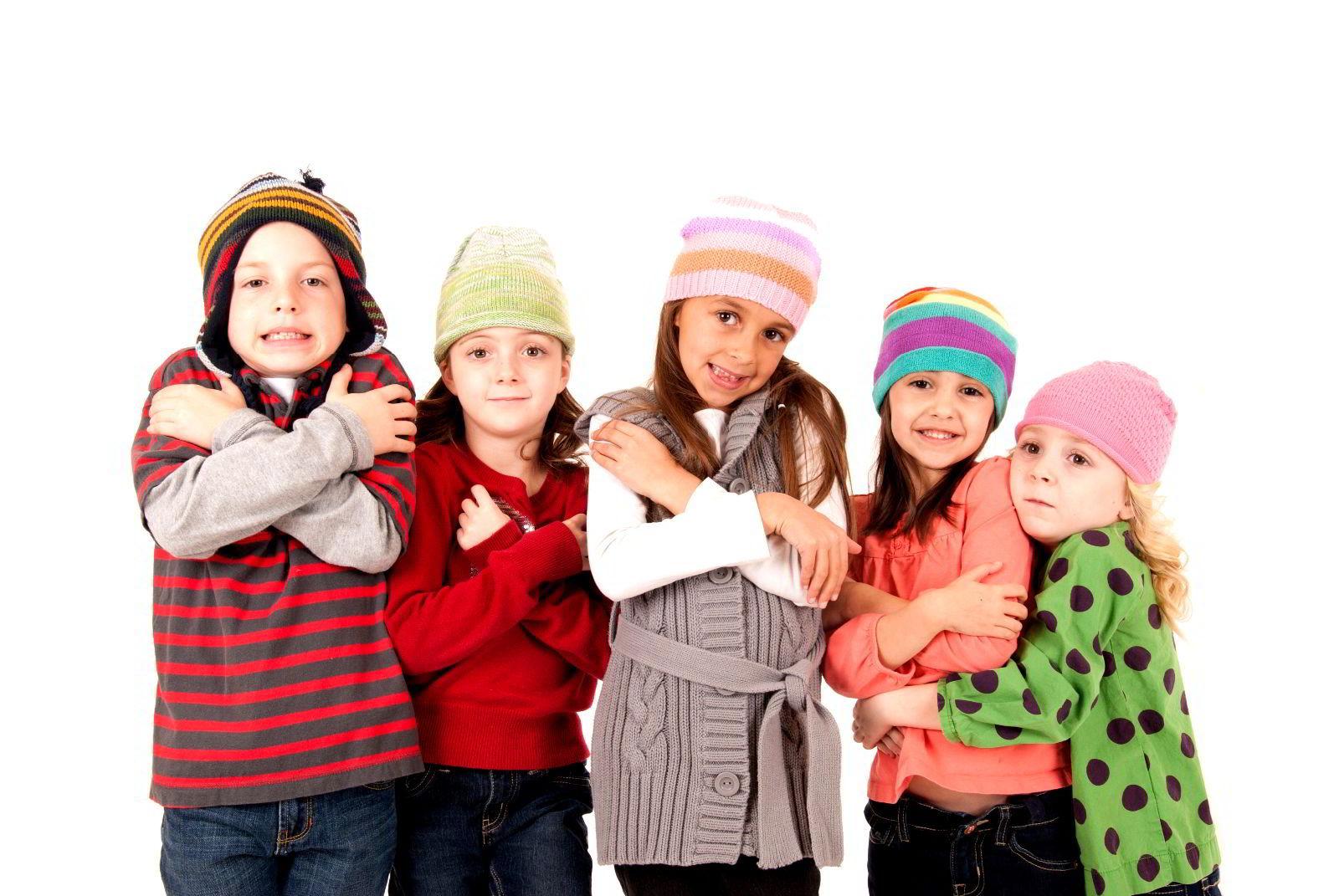 Niños abrigados con gorros expresando frio con su rostro