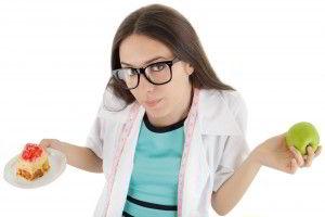 Mujer con bata blanca y anteojos sostenisdo un pastel en una mano y en la otra una manzana