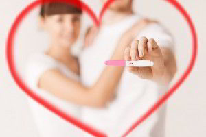 Un dibujo de corazon con una fotografía de un hombre y mujer con una prueba de embarazo en la mano