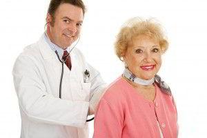 Adulto mayor sentado con médico revisando espalda con estetoscopio