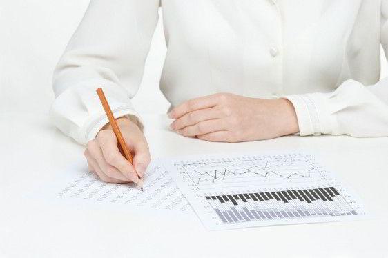 Acercamiento de la mano de una persona con camisa blanca escribiendo sobre graficas
