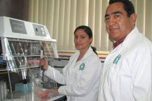 Un hombre u una mujer con bata blanca enfrente de un equipo de laboratorio
