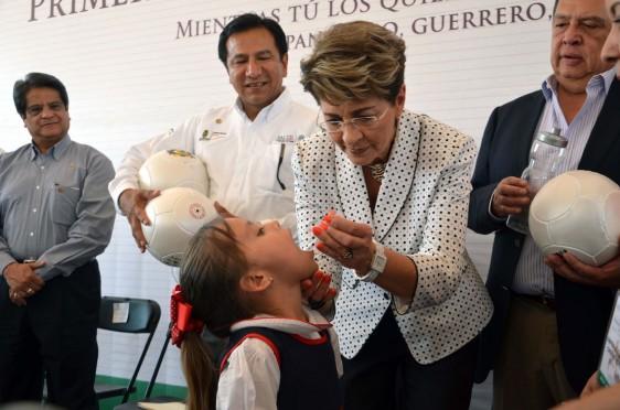 Mercedes Juan con gotero en la mano dejando caer gotas en la boca de una niña