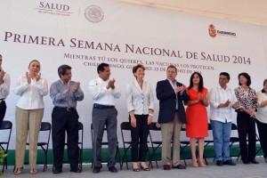 Mercedes Juan acompañada por personalidades atras letrero con texto primera Semana Nacional de Salud