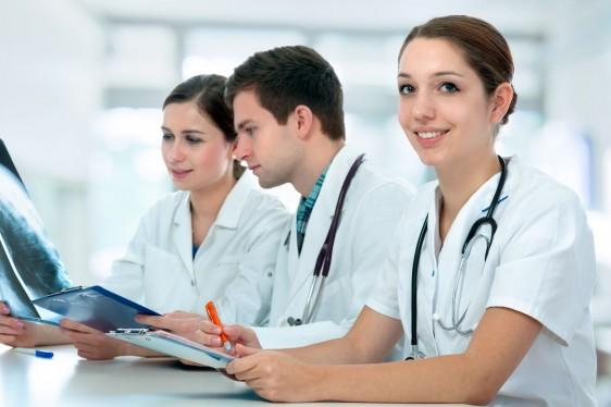 doctores en bata blanca con estetoscopios sentados y anotando