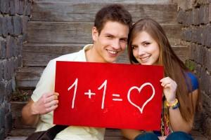 Dos jovenes con letrero rojo con texto 1 + 1 igual a amor