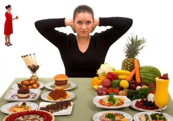 Mujer tapandose los oidos con un diablito a su derecha y con una mesa con comida enfrente a la isquierda pasteles hamburgesas a la derecha drutas y verduras