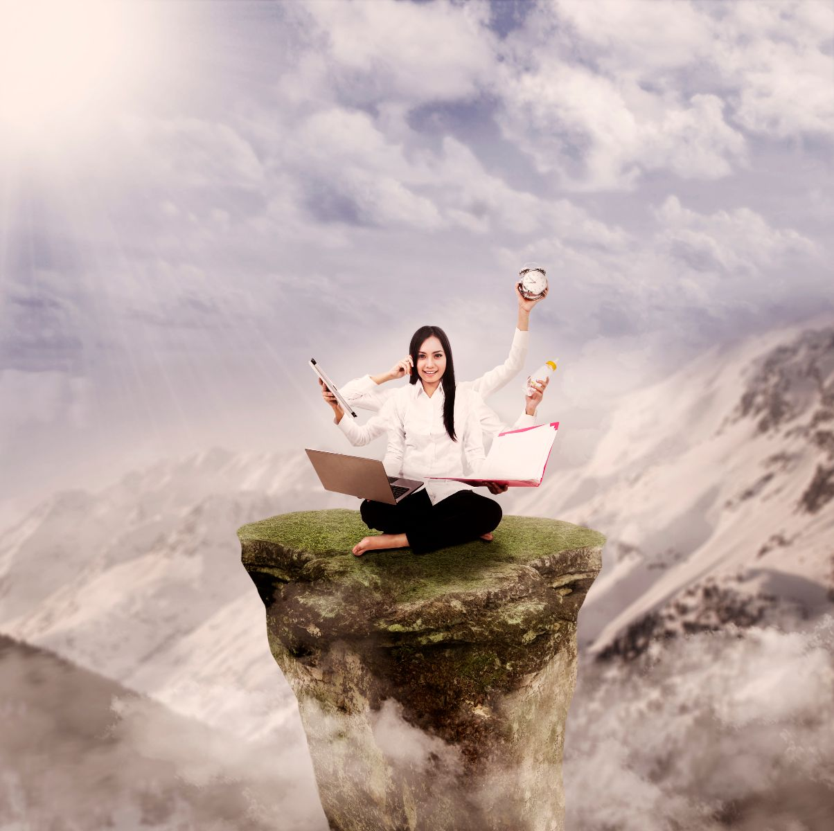 Mujer en la cima de una montaña con reloj, computadora, librera y teléfono en las manos en el fonod un cielo azul con montañas