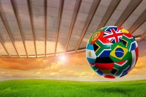 Balón de soccer con banderas del mundo, atardecer de fondo con un techo de cristal en un estadio