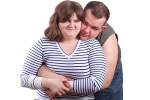 Hombre abrazando a mujer obesa con camisa azul a rayas