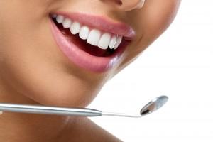 Acercamiento a los dientes de una mujer con un espejo de dentista