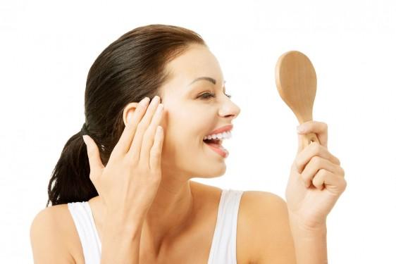 Mujer de cabello negro con un acercamiento a su rostro mirando un espejo y rocando su rostro y sonriendo