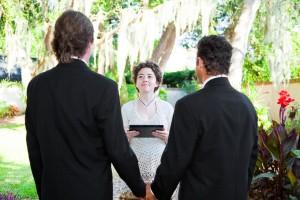 dos hombres vesitdos de negro frente a mujer vestida de blanco en una ceremonia de matrimonio