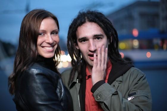 Mujer sonriendo y hombre sorprendido en el fondo una calle en al anochecer