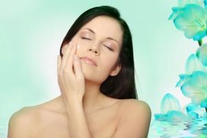 Mujer acariciandose el rostro en un fondo color aqua