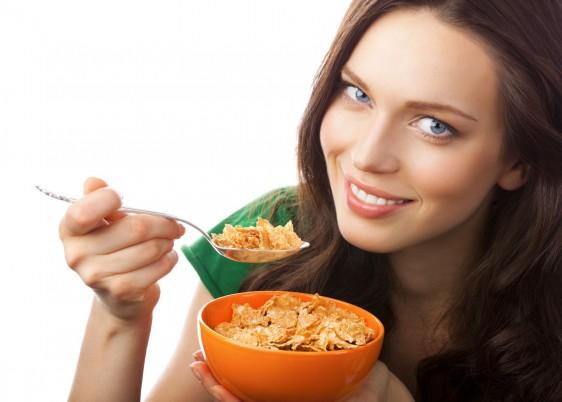 Mujer sonriendo con camisa verde y con una cuchara en la mano, con la otra sosteniendo plato hondo naranja que contiene cereal