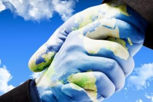 Dos manos saludandose pintadas con la tierra con un cielo azul en el fondo