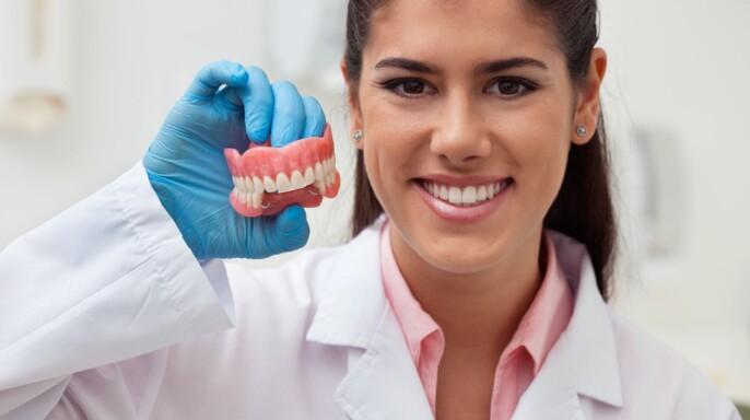 Dentista con bata blanca sonriedo y sostenido una muestra de dientes en la mano